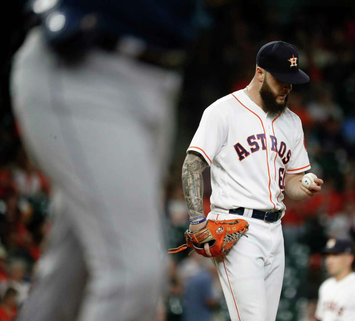 Houston Astros starting pitcher Dallas Keuchel (60) looks at the ball after walking Seattle Mariners Ryon Healy during the first inning of an MLB baseball game at Minute Maid Park, Wednesday, September 19, 2018, in Houston.