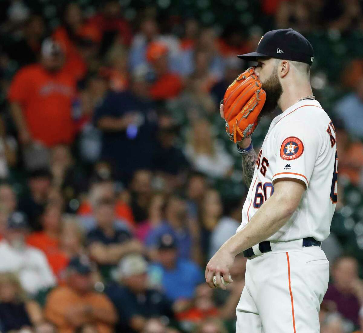Houston Astros starting pitcher Dallas Keuchel (60) covers his face with his glove during the first inning of an MLB baseball game at Minute Maid Park, Wednesday, September 19, 2018, in Houston.