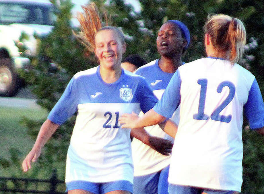 LCCC's Emma Lucas (21) is congratulated by teammates Boitumelo Rabale, center and Kassidy Louvall after scoring the game-wining goal for the Trailblazers in Wednesday's 3-1 home victory over St. Louis Community College. Lucas is a freshman from Roxana. Photo: Pete Hayes | The Telegraph