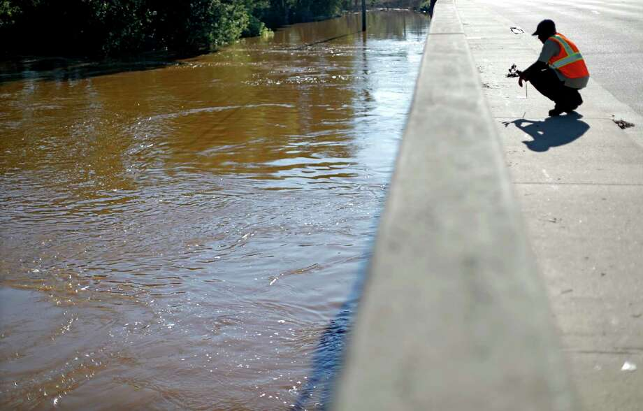 Maine Johnson with the city's communications department, takes photos of the Cape Fear River after its projected time of cresting in Fayetteville, N.C., Wednesday, Sept. 19, 2018. (AP Photo/David Goldman) Photo: David Goldman / 2018 Associated Press. All rights reserved.