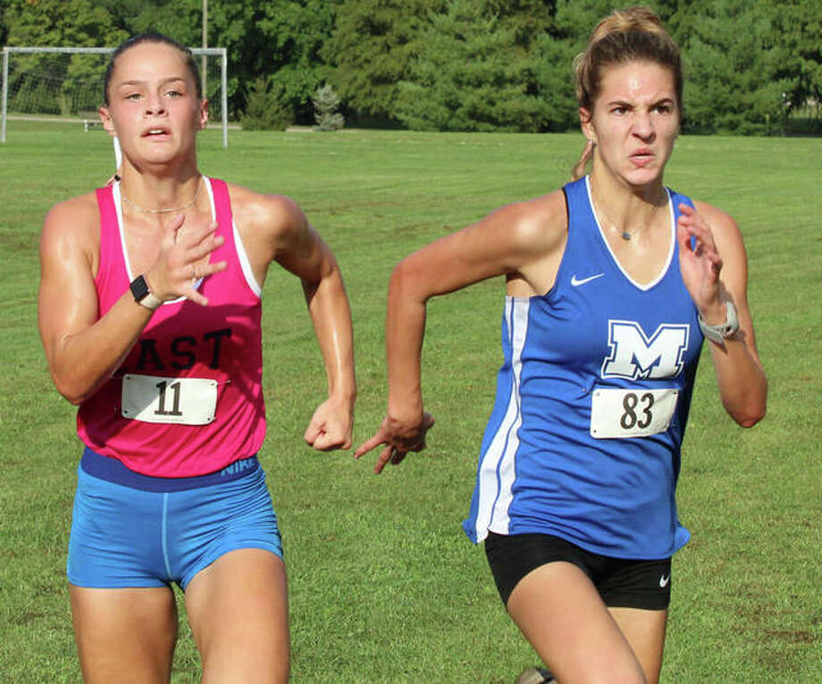 Belleville East's Hannah Eastman (left) and Marquette Catholic's Riley Vickrey sprint the final yards to the finish Wednesday at the Alton Invitational cross country meet at Moore Park in Alton. No results were released and entire field was disqualified after a wrong turn left all the girls about a mile short on the three-mile layout. Photo: Greg Shashack | The Telegraph