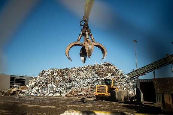 A grab claw passes a mound of metal at Schnitzer Steel's recycling yard on Monday, Sept. 17, 2018, in Oakland, Calif. The facility sits adjacent to a proposed location for a new Oakland Athletics ballpark.
