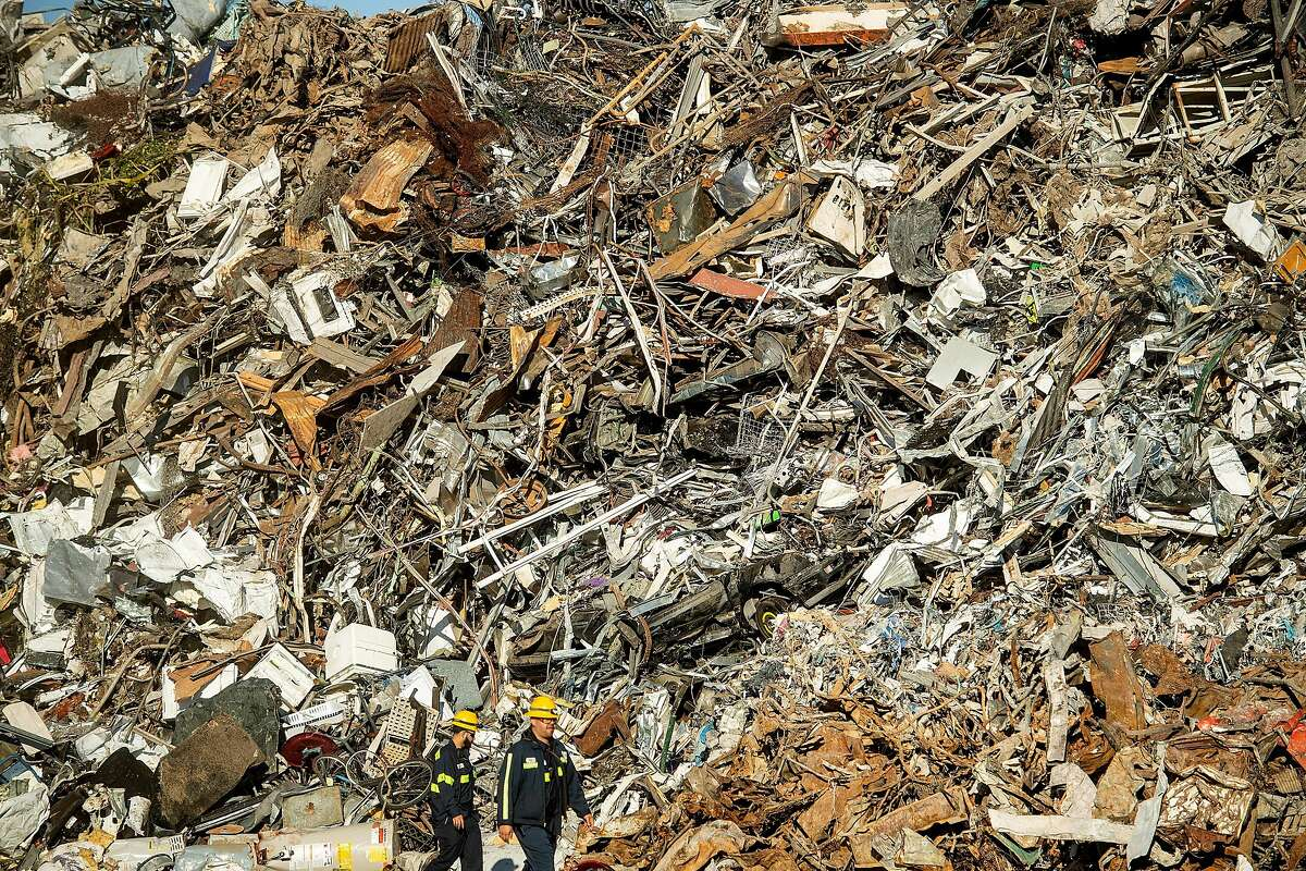 Workers pass scrap metal at Schnitzer Steel's recycling yard on Monday, Sept. 17, 2018, in Oakland, Calif. The facility sits adjacent to a proposed location for a new Oakland Athletics ballpark.