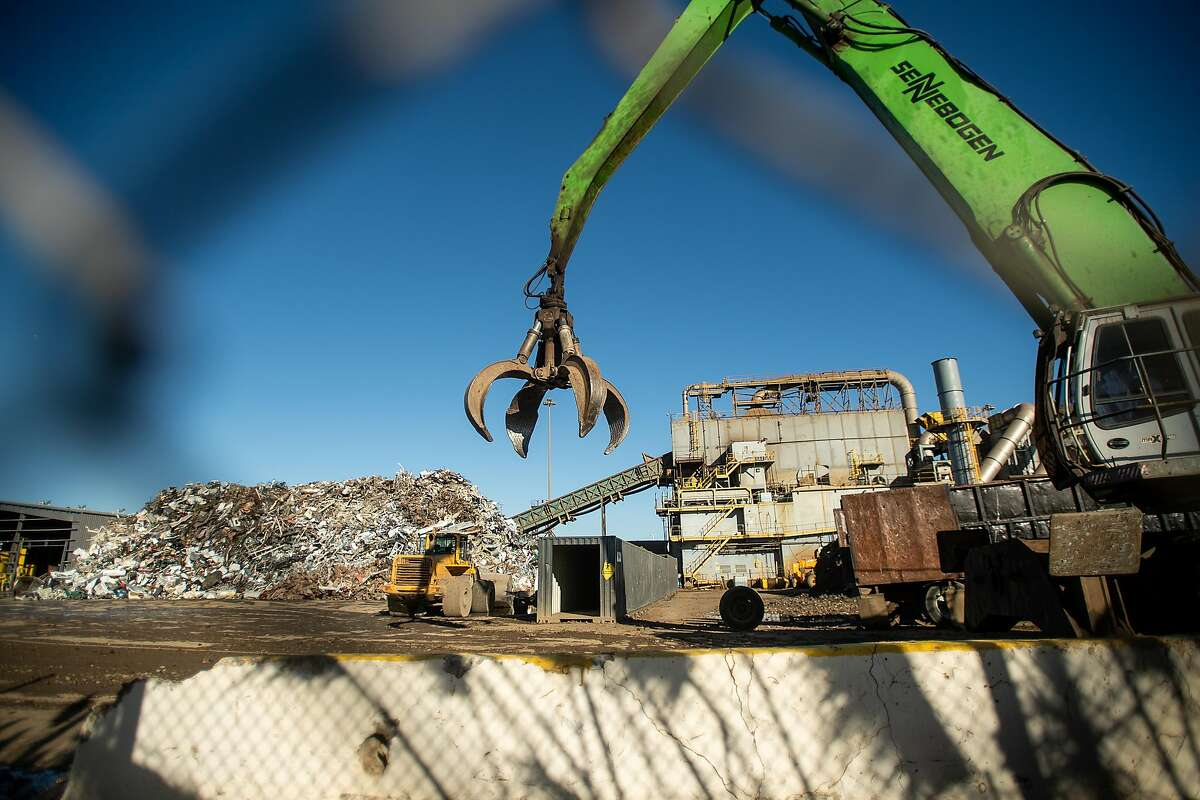 A crane with a grab claw traverses Schnitzer Steel's recycling yard on Monday, Sept. 17, 2018, in Oakland, Calif. The facility sits adjacent to a proposed location for a new Oakland Athletics ballpark.