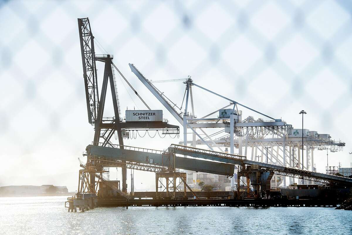 A crane and a conveyor belt rise over the Oakland Estuary at Schnitzer Steel's recycling yard on Monday, Sept. 17, 2018, in Oakland, Calif. The facility sits adjacent to a proposed location for a new Oakland Athletics ballpark.