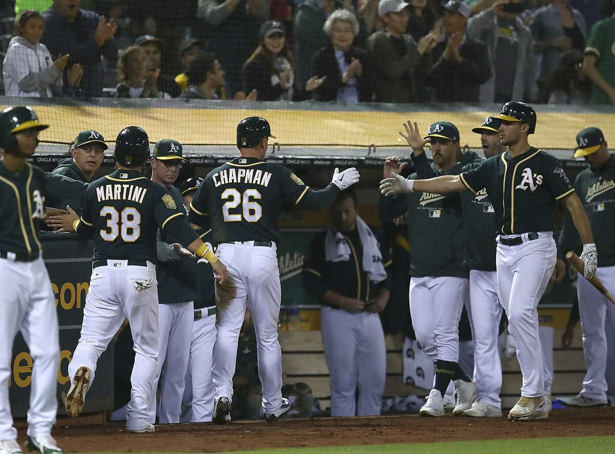 Oakland Athletics' Matt Chapman (26) and Nick Martini (38) are congratulated after scoring against the Los Angeles Angels during the fourth inning of a baseball game Wednesday, Sept. 19, 2018, in Oakland, Calif. (AP Photo/Ben Margot)