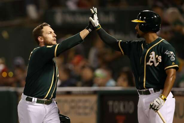 OAKLAND, CA - SEPTEMBER 19: Jed Lowrie #8 of the Oakland Athletics is congratulated by Marcus Semien #10 after he scored in the fourth inning on a hit by Stephen Piscotty #25 against the Los Angeles Angels at Oakland Alameda Coliseum on September 19, 2018 in Oakland, California. (Photo by Ezra Shaw/Getty Images)