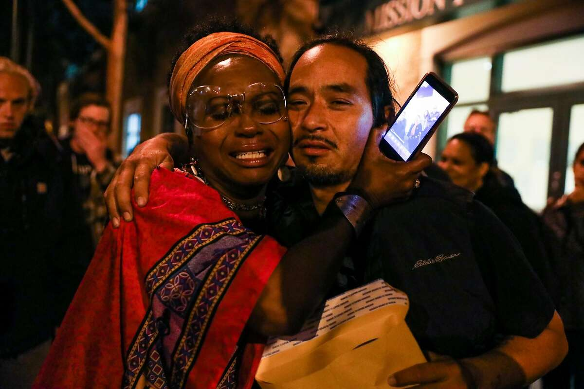 Ilyich Sato (right) is embraced Asale Chandler after he was briefly detained by the police in San Francisco, California, on Wednesday, Sept. 19, 2018.