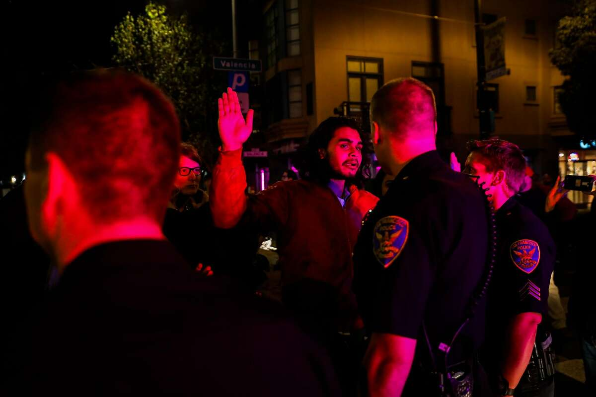 A protester waves his hands in the air at the police after being asked to step back at 17th and Valencia Streets after a man was detained by the police for allegedly filming an arrest in San Francisco, California, on Wednesday, Sept. 19, 2018.