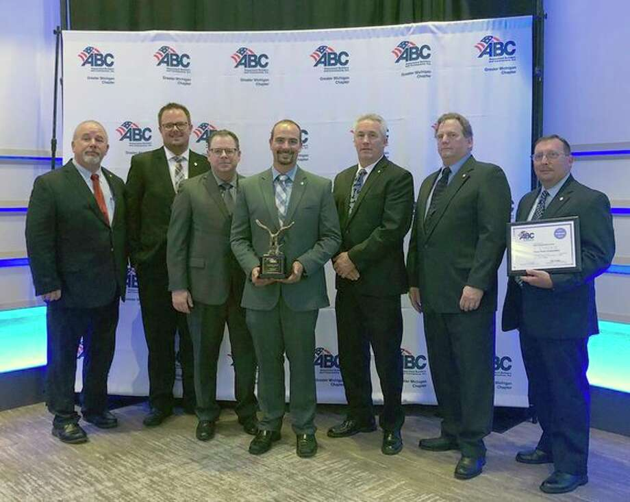 From left, Paul Crivac, Chris Moultrup, Jon Lynch, Mike Sosnofsky, Brian Hawkins, Ted High and Brian Powers of Three Rivers Corp. accept an award from the Associated Builders and Contractors Greater Michigan Chapter. (Photo provided)