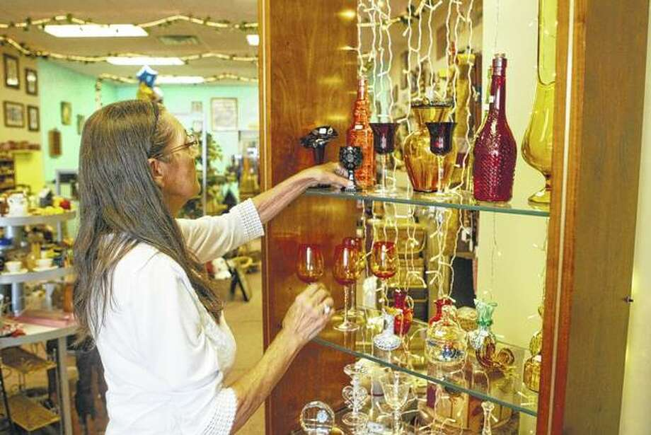 Jackie Branscum moves some glassware in her new resale store, The Rabbit Hole, at 303 W. State St. Photo: Greg Olson | Journal-Courier