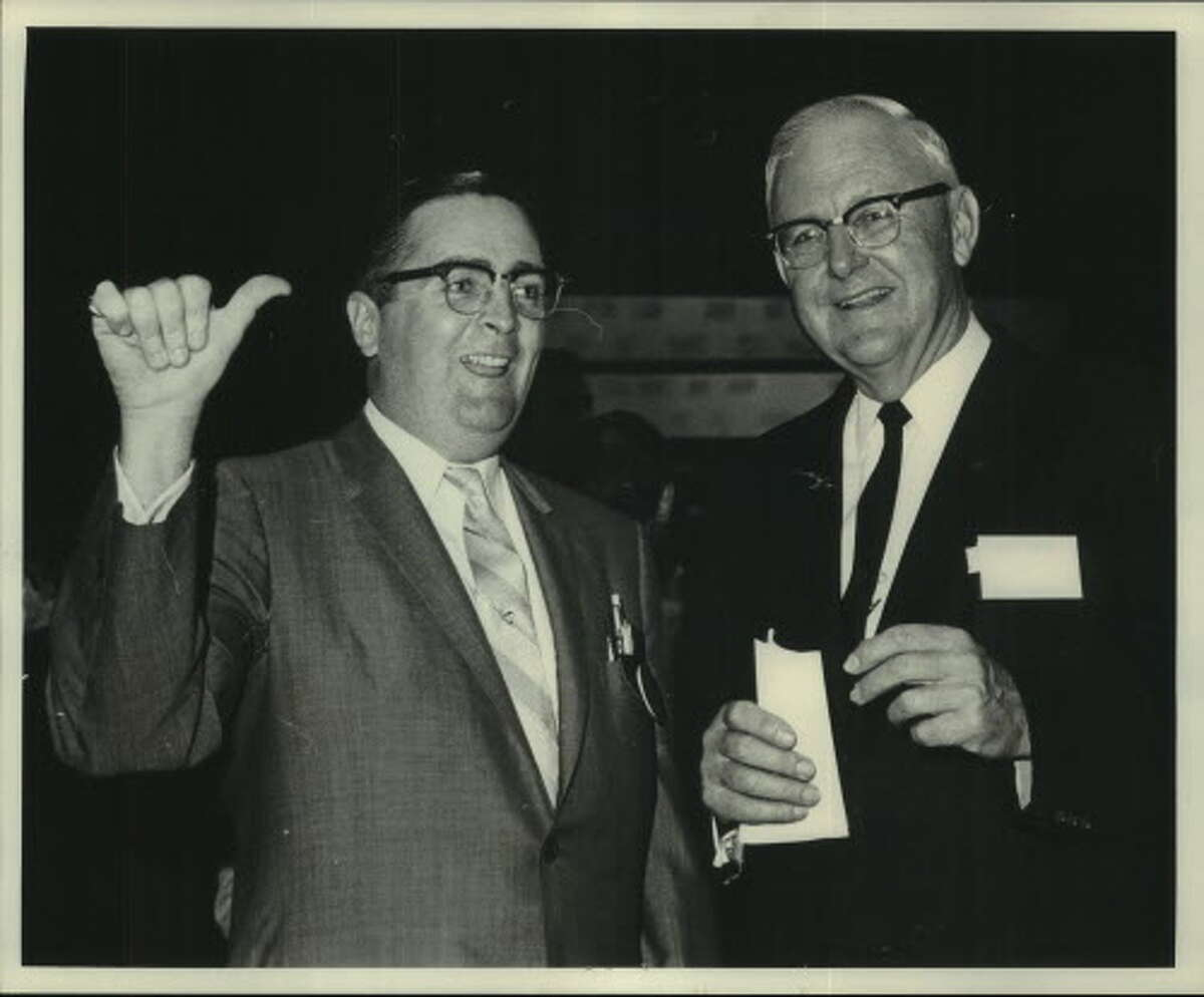 Carothers and a floor officer with the American Stock Exchange celebrate Allright's inclusion on the exchange in 1965 in New York.