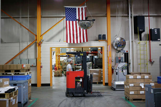 An American flag hangs above a worker operating a forklift at the Stihl Inc. manufacturing facility in Virginia Beach, Virginia, on Jan. 11, 2018.