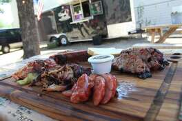 A collection of meats from Bad To The Bone BBQ with the trailer in the background. Bad To The Bone is now closed for business after starting up in 2016.