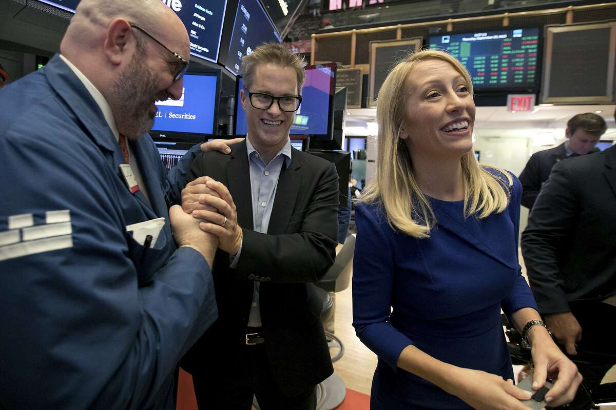Eventbrite Chairman Kevin Hartz, center, is welcomed by Specialist Peter Giacchi, left, as he and company CEO Julia Hartz, start Eventbrite's IPO process on the floor of the New York Stock Exchange, Thursday, Sept. 20, 2018. (AP Photo/Richard Drew)