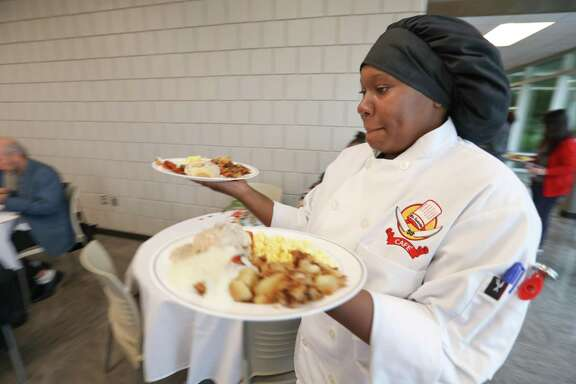 Stafford High Culinary Arts student TeKylah Simpson carries breakfast plates for the VIP's Friday, Sept. 14, 2018, in Stafford. Stafford High Culinary Arts program has allowed TeKylah Simpson many once in a lifetime opportunities. Not only has she learned how to prepare world-class meals, but she also was the first person in her family to travel outside of the United States when she ventured to Italy with the program. The Stafford High senior has now been accepted into a culinary arts program in Austin.