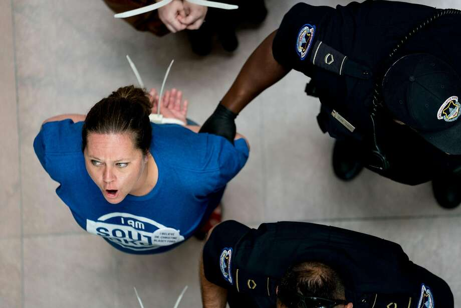 Demonstrators are arrested while chanting �we believe Anita Hill, we believe Christine Ford� outside the office of Sen. Chuck Grassley (R-Iowa) on Capitol Hill in Washington, Sept. 20, 2018. Christine Blasey Ford is reportedly prepared to testify next week about her accusation of sexual assault against Brett Kavanaugh. (Erin Schaff/The New York Times) Photo: ERIN SCHAFF, NYT