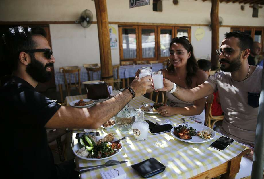 In this Saturday Sept. 8, 2018 photo, Lebanese raise their glasses of arak in a toast during a festival that celebrates Lebanon's national alcoholic drink, in the town of Taanayel, east Lebanon. The anise-tinged arak, is surrounded by ritual -- from its distilling down to the moment when it's mixed, turning milky white in water, and drunk over long, lingering meals. (AP Photo/Hussein Malla) Photo: Hussein Malla / Associated Press