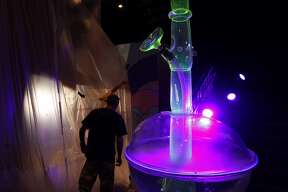 In this Tuesday, Sept. 18, 2018 photo, a man walks by a 24-foot-tall bong at the Cannabition cannabis museum in Las Vegas. The museum celebrating all things cannabis with displays that include a glass bong taller than a giraffe and huggable faux marijuana buds is the newest tourist attraction in Las Vegas. (AP Photo/John Locher)