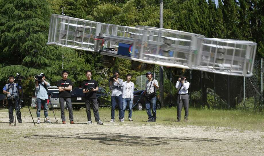 In this Saturday, June 3, 2017, file photo, Tsubasa Nakamura, project leader of Cartivator, third from left, watches the flight of the test model of the flying car on a former school ground in Toyota, central Japan. The Japanese government has started a flying car project, bringing together more than a dozen companies, including All Nippon Airways, electronics company NEC, Toyota-backed startup Cartivator and Uber, the ride-hailing service. Toyota and its group companies have also invested 42.5 million yen ($375,000) in a Japanese startup, Cartivator, that is working on a flying car. Photo: Koji Ueda /Associated Press / Copyright 2018 The Associated Press. All rights reserved.