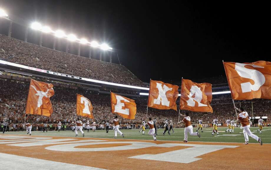 PHOTOS:College football coaches salary (2019) AUSTIN, TX - SEPTEMBER 15:  Texas Longhorns cheerleaders run with flags during the game between the Texas Longhorns and the USC Trojans at Darrell K Royal-Texas Memorial Stadium on September 15, 2018 in Austin, Texas.  (Photo by Tim Warner/Getty Images) >>>Browse through the photos to see the highest-paid college football coaches ... Photo: Tim Warner/Getty Images