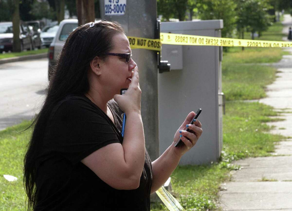 Resident Victoria Rivera watches as Bridgeport police officers investigate at the scene of a shooting on Norman Street in Bridgeport, Conn., on Thursday Sept. 20, 2018.