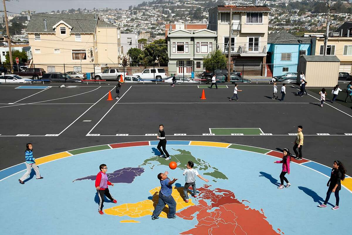 Monroe Elementary School students play on a world map in the school playground during recess in San Francisco.