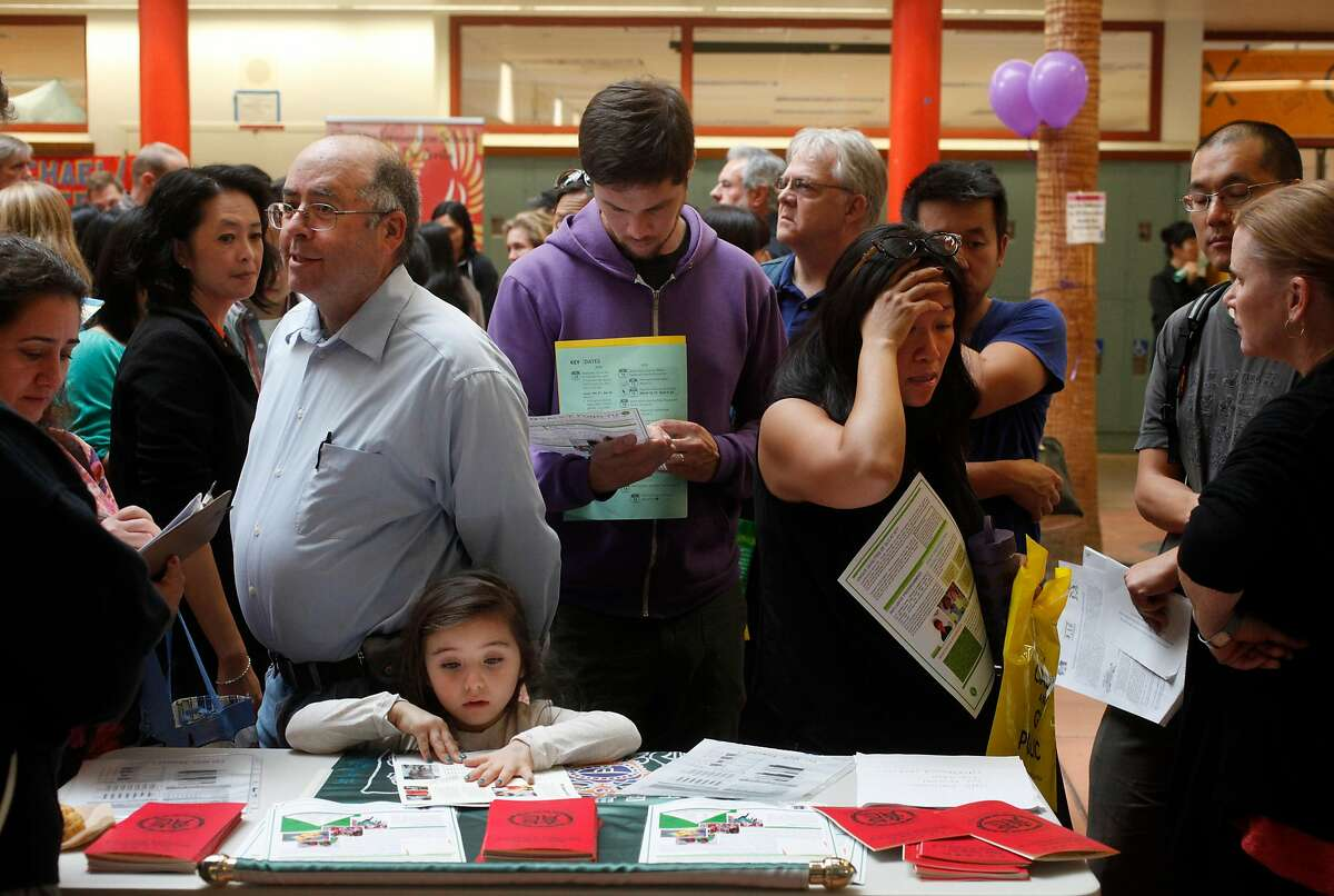 Parents and school representatives discuss details at the SFUSD school enrollment fair at John O'Connell High School on Oct. 25, 2014 in San Francisco.