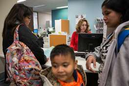 Lia Tamayo (left), case manager for Jenn Reyes (right) and her son John Vincent La Pena, 6, consults with Margarita Guardado, intake placement assistant, at the Administration Offices for the School District. Reyes and her son, both of whom arrived to the United States from the Philippines two weeks ago, came to the school district office for her son's school registration. Thursday, September 20, 2018 in San Francisco Calif.