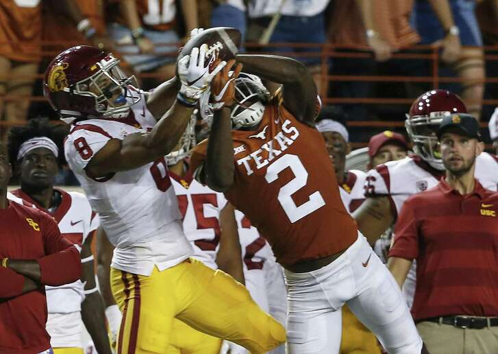 Texas cornerback Kris Boyd, right, wins a jump ball with USC receiver Amon-Ra St. Brown on Saturday. The interception lead to a field goal that helped turn the momentum in UT's favor.