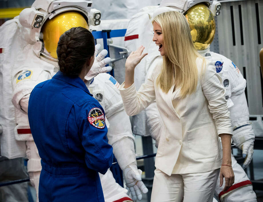 Ivanka Trump, the president's daughter and senior adviser, high fives a space suit as astronaut Nicole Mann gives her a tour of the Space Vehicle Mockup Facility during a visit to NASA's Johnson Space Center on Thursday, Sept. 20, 2018, in Houston.  