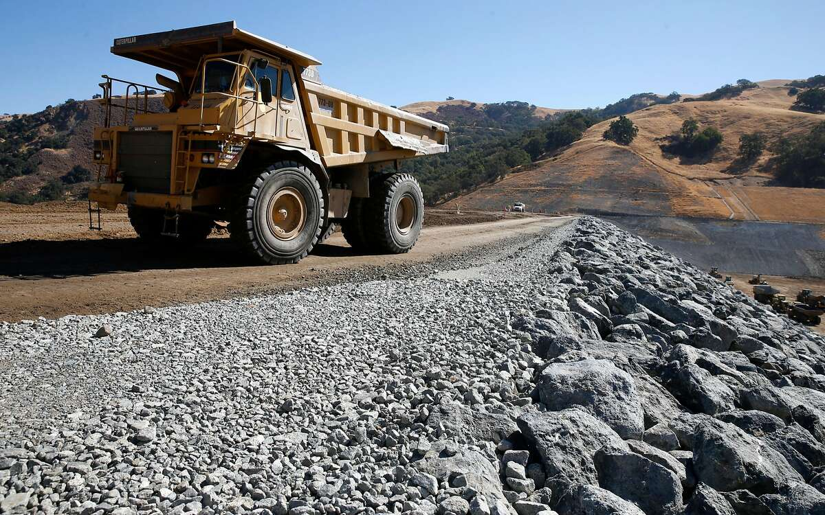 Heavy trucks transport rocks and boulders across the top of the new Calaveras Dam in Fremont, Calif. on Wednesday, Sept. 19, 2018. The extensive reconstruction project of the dam, which broke ground in 2011, is nearing completion and is on target to begin filling with water sometime this winter.