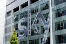 FILE - This Friday, July 25, 2014, file photo shows a view of the headquarters of the Italian Sky television broadcaster in Milan, Italy. British regulators say that the corporate battle between 21st Century Fox and Comcast to take over broadcaster Sky will be settled by auction, commencing at 5 p.m. on Sept. 21 and ending on the evening of Sept. 22, 2018. (AP Photo/Luca Bruno, File)