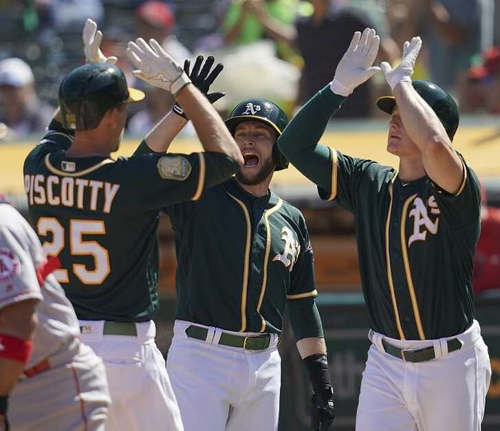 Stephen Piscotty is congratulated by Jed Lowrie, center, and Matt Chapman after Piscotty hit a three-run home run in the bottom of the third inning.