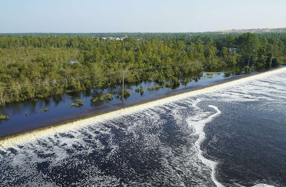 Flooding from Cape Fear River overtops an earthen dike. Duke Energy said a dam had been breached, making it possible for coal ash from an adjacent dump to flow into the river. Photo: Associated Press