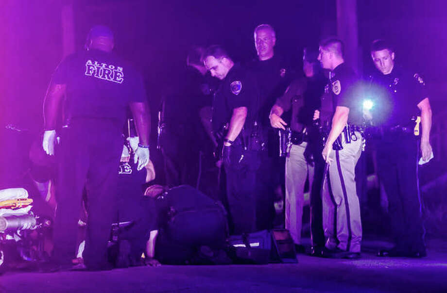 Paramedics and Alton firefighters treat one of three victims of an Aug. 29 shooting in the 100 block of West 19th Street as Alton police and Madison County deputies process the scene. Photo: Nathan Woodside | Telegraph File Photo