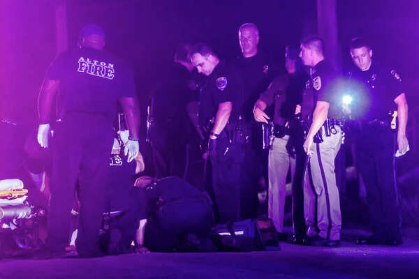 Paramedics and Alton firefighters treat one of three victims of an Aug. 29 shooting in the 100 block of West 19th Street as Alton police and Madison County deputies process the scene.