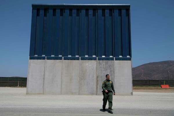 Border Patrol Public Affairs Officer Vincent Pirro looks at border wall prototypes that stand in the San Diego sector of the border wall on April 25.