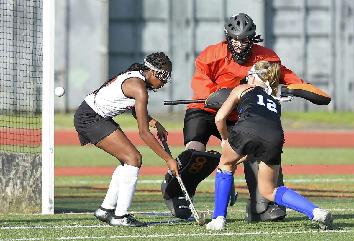 Darien's Sarah Bogdan (12) fires a shot past Stamford goalkeeper Kristen D'Ariano and Christina Sauveur (2), scoring in the second half of an FCIAC girls field hockey game at Boyle Stadium in Stamford, Connecticut on Sept. 20, 2018. Darien won 11-1.