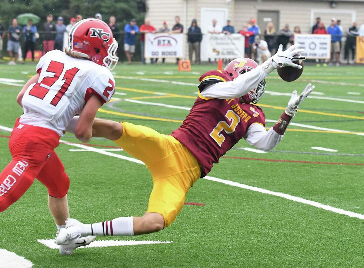 St. Joseph?'s Jesse Bike, right, makes a reception for a first down in front of New Canaan?'s Nate Sibbett during their football game at St. Joseph?'s, Sept. 8, 2018.
