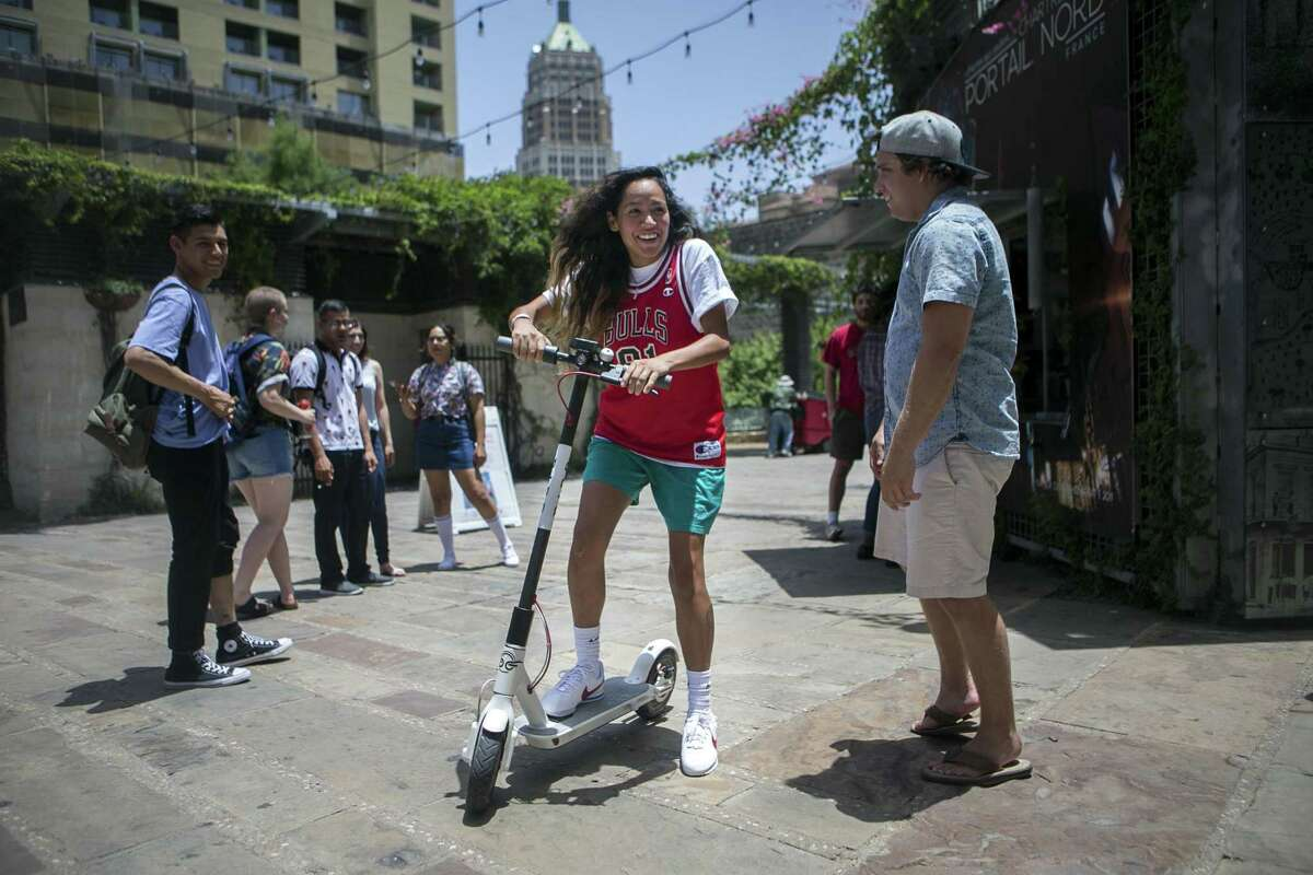 April Galindo of Austin hops on an electric Bird scooter in Main Plaza in downtown San Antonio on July 1, 2018. There are several thousand in the city now.