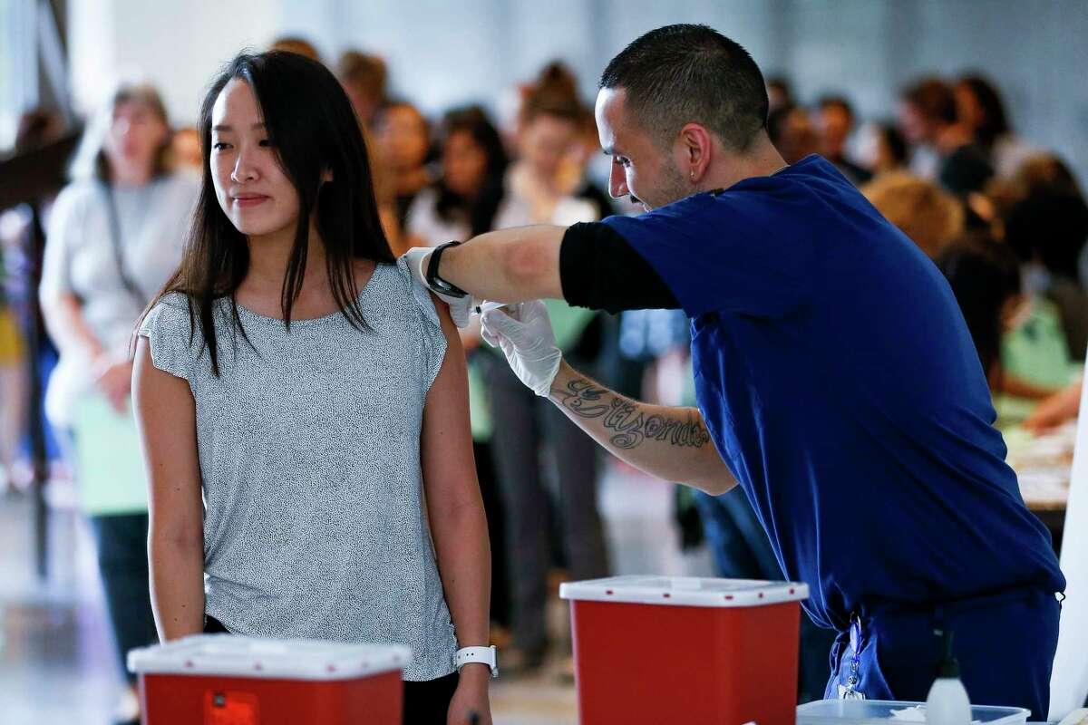 Baylor College of Medicine employee Taylor Nguyen, left, receives a flu shot from Occupational Health Medical Assistant Nick Elizondo as hundreds of BCM employees wait to get their free vaccinations before the start of the flu season Thursday Sept. 20, 2018 in Houston.