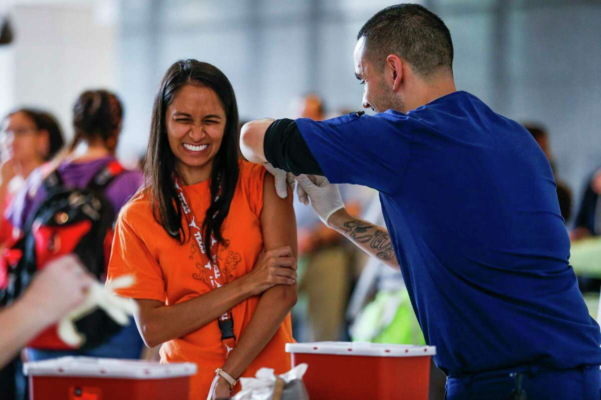 Baylor College of Medicine resident Rachna Patel, left, reacts as she receives a flu shot from Occupational Health Medical Assistant Nick Elizondo as hundreds of BCM employees wait to get their free vaccinations before the start of the flu season Thursday Sept. 20, 2018 in Houston.