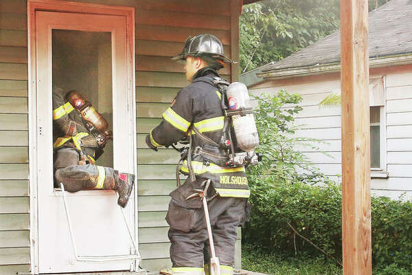 An Alton firefighter climbs through the front screen door of a house Wednesday evening at 909 Rixon St. in Alton after an Alton police officer helped kick in the front door of the condemned house. A fire was burning in a bedroom of the house, which was not occupied. It is another in a rash of fires in vacant and condemned houses in Alton. A reward still stands for information leading to an arrest in the fires of vacant houses in the city. No injuries were reported, and Alton firefighters were able to quickly extinguish the fire.