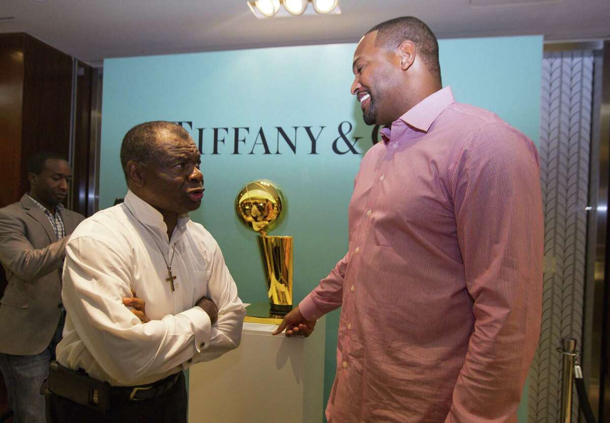 Two former Rockets greats - Calvin Murphy, left, and Robert Horry - flank a replica of the Larry O'Brien Trophy.