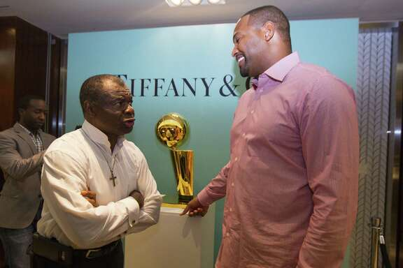 Two former Rockets greats — Calvin Murphy, left, and Robert Horry — flank a replica of the Larry O'Brien Trophy.