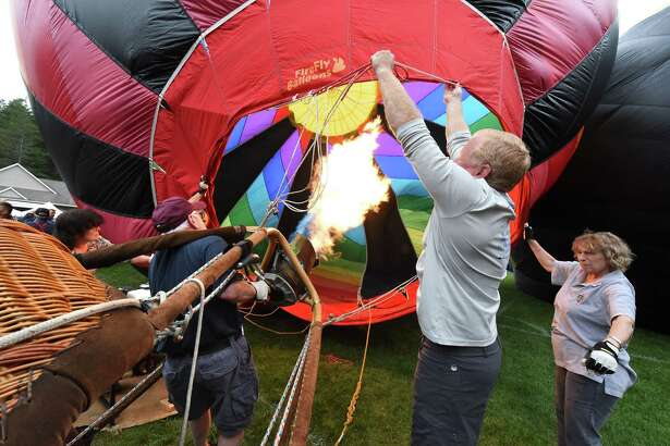 """Pilot Rick Silva, second from left, blows up his hot air balloon """"High At Last"""" with his crew Norm Fay, second from right, and Carol Silva, right, during the kickoff of the 2018 Adirondack Balloon Festival at Crandall Park on Thursday, Sept. 20, 2018 in Glens Falls N.Y. (Lori Van Buren/Times Union)"""