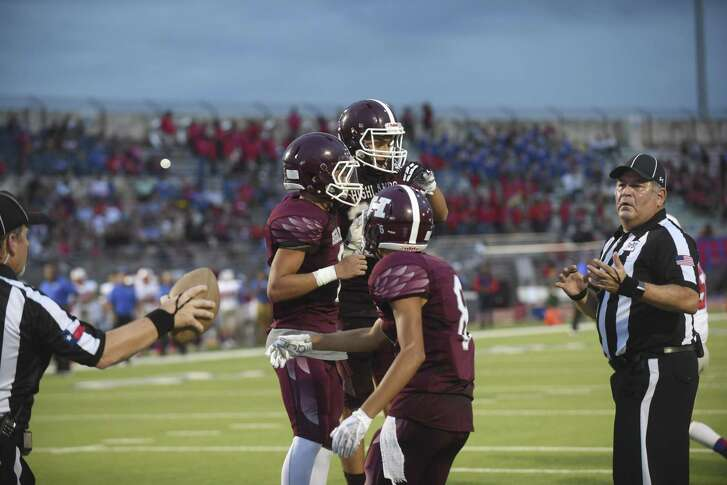 Running back Nigel Cervantes, left, celebrates with Highlands teammates Bradley Cavanaugh, top, and Eric Rodriguez after scoring a first-half touchdown against Jefferson at Alamo Stadium on Thursday, Sept. 20, 2018.