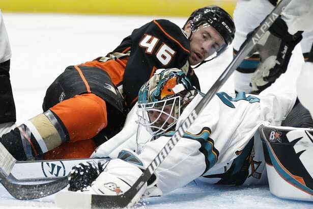 San Jose Sharks goaltender Aaron Dell, front, grabs the puck in front of Anaheim Ducks' Ben Street during the second period of a preseason NHL hockey game Thursday, Sept. 20, 2018, in Anaheim, Calif. (AP Photo/Jae C. Hong)