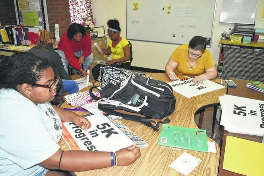 Illinois School for the Deaf juniors Olivia Scott of Chicago (left) and Ivy Bliss of Kewanee make road signs Thursday for ISD's Glow and Go 5K, a fundraising event that begins at 6:30 p.m. today. Photo: Greg Olson   Journal-Courier